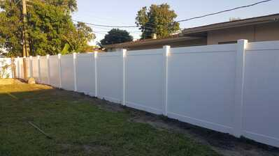 this picture is of a new white fence surrounding a property and completed by Fort Lauderdale Pavers